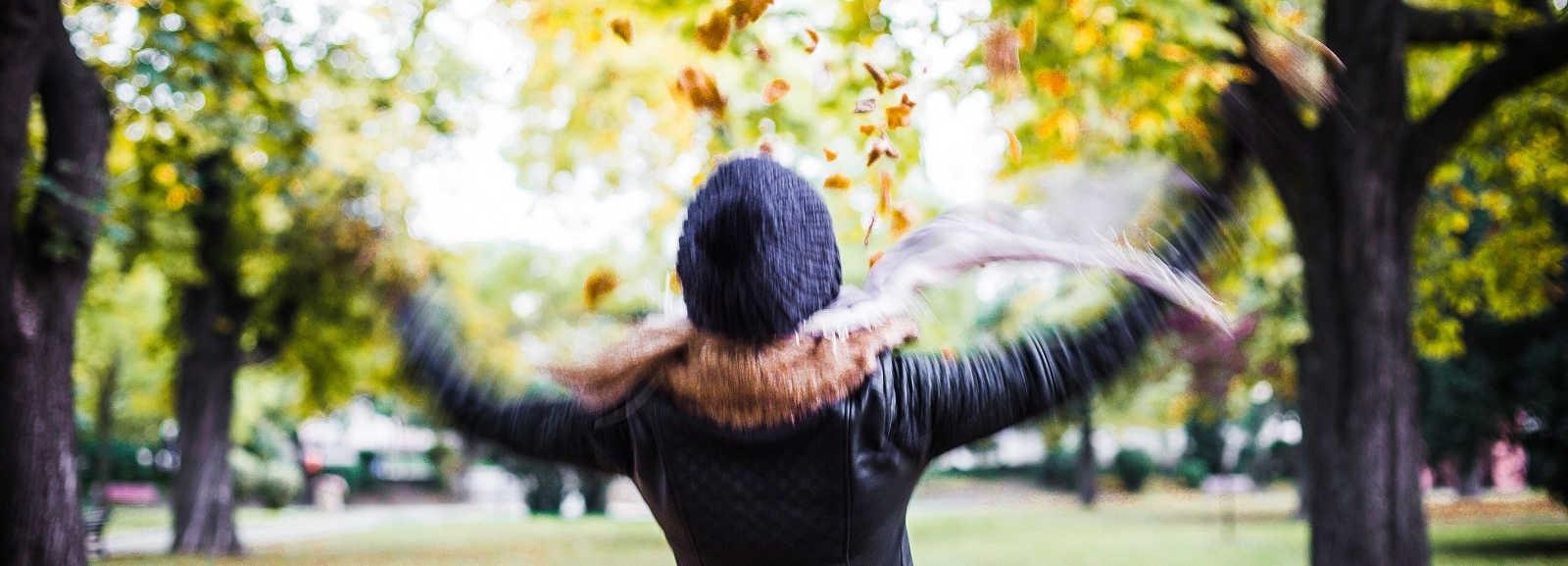 Flicka kastar löv